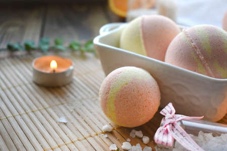 Spa resort setting. Still life image with bath bombs and candle on wooden background. Spring or summer relax concept. Banco de Imagens