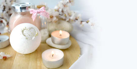 Romantic spa with bath bomb, cosmetic scrub, candles and cherry blossom. Still life skincare products. Resort concept for Valentines day, Mothers day or wedding greeting card. Banco de Imagens