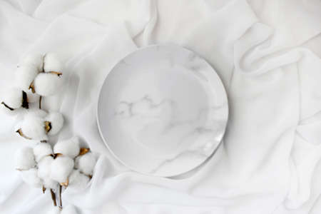 Empty marble plate with cotton flowers on white silk background. Elegant minimalist wedding table setting. Top view. Stockfoto