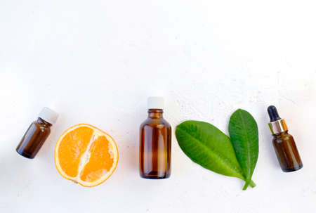 Mock up aromatherapy flatlay with orange essential oil bottles, citrus and leaves on white background. Spa, natural cosmetic and healthcare concept. Detox, anti-cellulite effect. Top view. Copyspace.