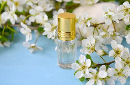与精油或香水瓶的春天芳香疗法概念在开花在蓝色背景。水疗中心豪华化妆品和美容博客。情人节,母亲节或婚礼贺卡。
