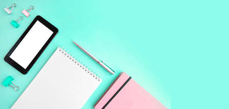 Feminine office flatlay with empty notepad, smartphone and stationery on mint background. Online education or blogging concept. Trendy design. ... Header with copy space Zdjęcie Seryjne