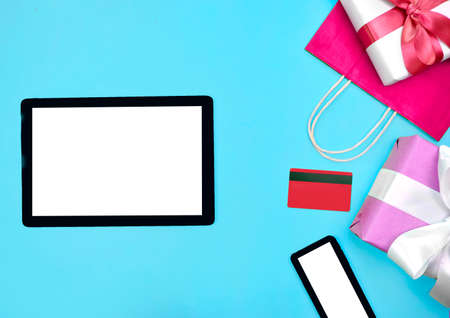 Mock up flat lay with tablet, smartphone, credit card, gift boxes on blue background. Online shopping concept. Greeting card for Christmas, Valentines day and Mothers day. Stock fotó