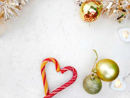 Mock up Christmas holiday flatlay. Heart candy cane, decoration balls, tinsel oj white background.