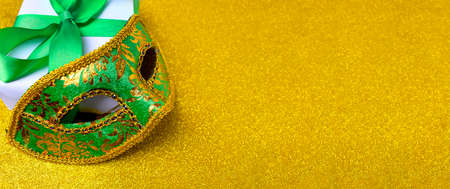 Ornate carnival mask, gift box on glitter golden background. Mardi gras festive celebration banner with copy space.