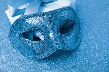 Close up carnival mask on sparkle background. Trend color 2020 blue. Mardi gras or festive concept.