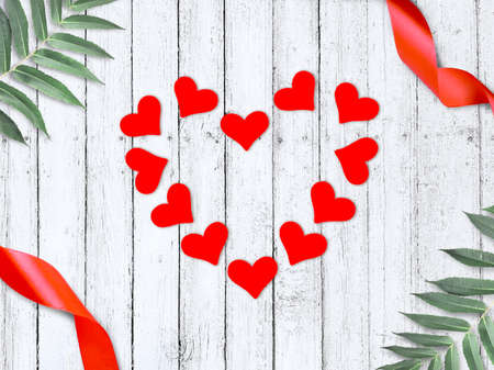 Love greeting composition with frame made red hearts, ribbons and palm leaves on wooden background. Valentines day, Mothers day or wedding flatlay with copyspace.