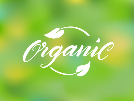 organic background: Organic brush lettering against blurred background. Hand drawn word organic with leaves. Label, logo template for organic products, healthy food markets.