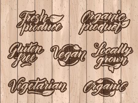 Retro gestileerde gezonde voeding beletteringen. Etiket, logo template gestileerde met stempel effect op een houten achtergrond. Organisch, biologisch product, glutenvrij, veganistisch, lokaal geteelde, vegetarisch, verse producten. Eps 10 vector. Textuur kan gemakkelijk worden verwijderd.