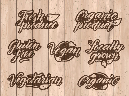 Retro styled healthy food letterings. Label, logo template stylized with stamp effect on a wooden background. Organic, organic product, gluten free, vegan, locally grown, vegetarian, fresh produce. Eps 10 vector. Texture can be easily removed. Illustration