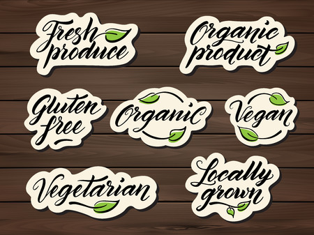 produces: Hand drawn healthy food letterings. Label, badge, logo template on a wooden background. Eps 10 vector.
