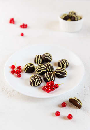 Chocolates with red currant berries on a white plate. No sugar, lactose, gluten. Imagens