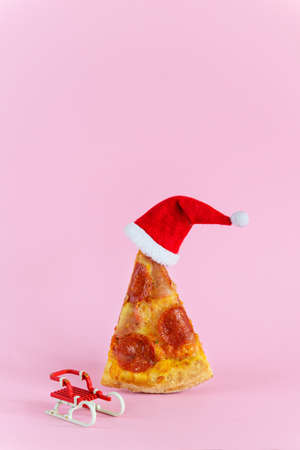 A slice of pepperoni pizza in the shape of a Christmas tree with a Santa's hat and a sleigh.
