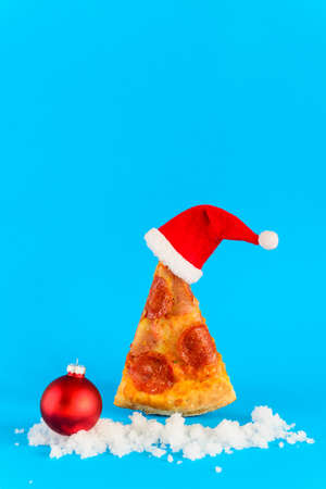 A slice of pepperoni pizza in the form of a Christmas tree with Santa's hat, sleigh and snow on a blue background.