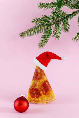 A slice of pepperoni pizza in the form of a Christmas tree with a Santa's hat, a Christmas ball and a spruce branch on a pink background.