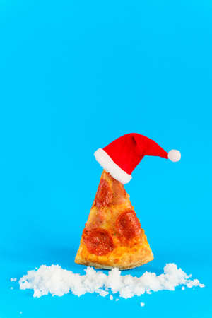 A slice of pepperoni pizza in the form of a Christmas tree with a Santa's hat and snow on a blue background.