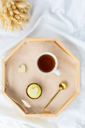Breakfast of cake with tea on a tray in bed with a bouquet of flowers. Valentine's day concept. Vertical orientation, top view.