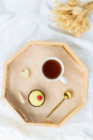 Cake with raspberry and a cup of tea on a tray and a bouquet of flowers on a white bed. Valentine's day concept. Sugar, lactose, gluten free. Horizontal orientation, top view.