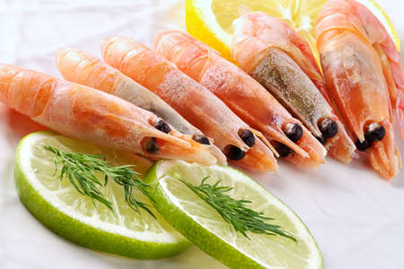 Shrimps laid out on a dish and seasoned by a lemon and spicy grasses-refined low-calorie snack Stock Photo