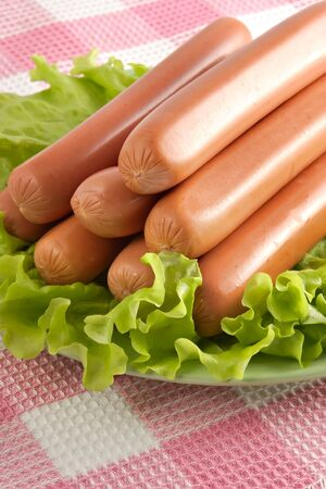 Appetizing pork sausages seasoned by green salad-product for preparation of hot dogs Archivio Fotografico