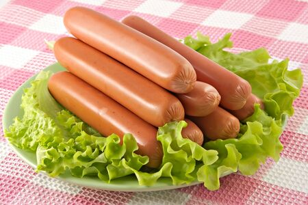 Appetizing pork sausages seasoned by green salad-product for preparation of hot dogs Stock Photo