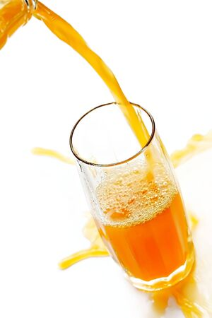 Jet of cold orange juice spills by a glass-impatience to satisfy thirst