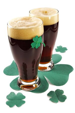 Dark Irish beer for St Paticks Day on napkins stylized under clover leaf