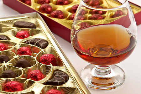 Glass with cognac and sweets with liquor isolated on a white background Stock Photo