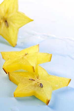Fruit abstraction-slices carambola on blue background, cut for preparation of cocktails