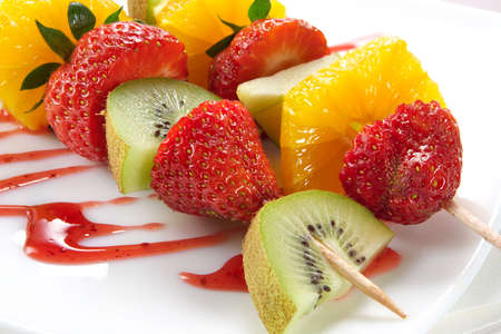 Fruit allsorts on skewers served atop of a plate decorated by strawberry jam