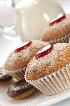 Appetizing fruitcakes and chocolate cookies decorated by powdered sugar and jam photo