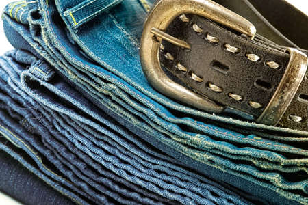 Vintage denim clothes-pile of jeans and leather belt photo