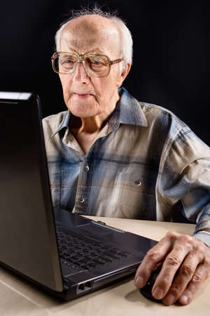 comprehension: Intellectual senior man works on the laptop late at night