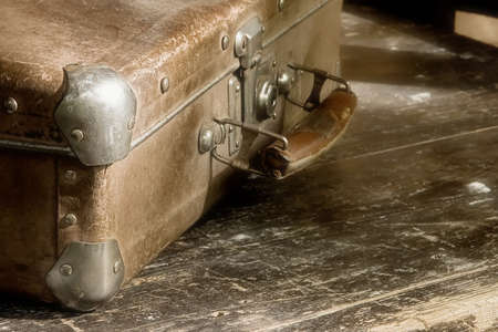 togs: Beloved  grunge trash-suitcase on the shabby table Stock Photo