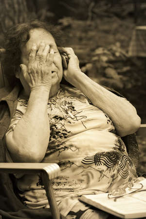 committed:  lonely old woman in deep depression speaks by mobile phone-thoughtfulness and sadness