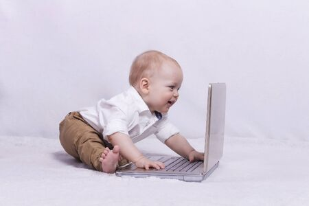 nappy new year: Cute baby boy looking something at laptop Stock Photo