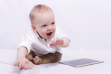 nappy new year: Smiling toddler boy playing with a tablet
