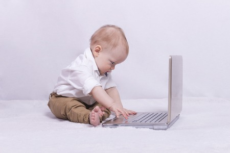 nappy new year: Concentrated baby boy playing in laptop. Concept of IT generation. Gamer.
