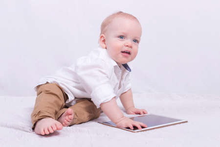 nappy new year: Adorable smiling infant boy playing with a tablet