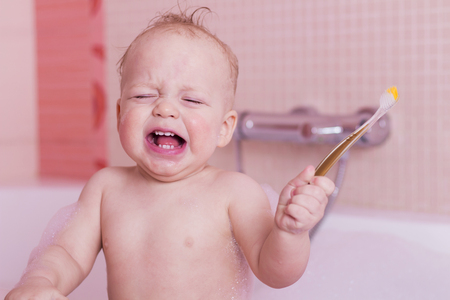 Crying baby boy with a teethbrush in a bathtub. Stock Photo