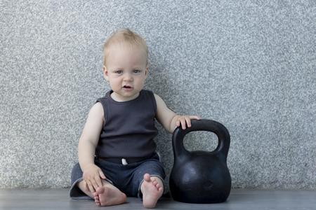 Müder kleiner Junge nach dem Pumpen von Eisen mit einer Kettlebell auf dem Boden sitzen Standard-Bild