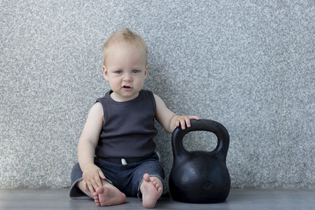 Tired little boy after pumping iron with a kettlebell sitting on the floor Archivio Fotografico