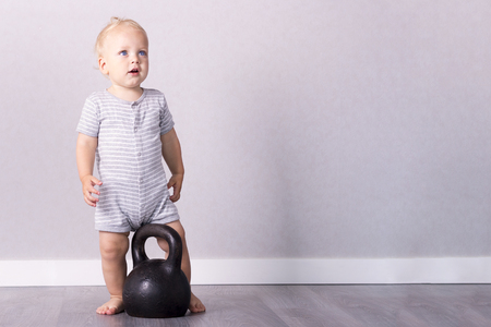 Adorable toddler in retro style sport suit going to lift a kettlebell Foto de archivo