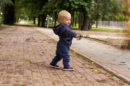 Cute toddler with a drawn rapier. Funny baby boy in the park with a pictured epee