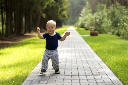 Babys の最初のステップです。最初の独立した手順。散歩にかわいい男の子 写真素材