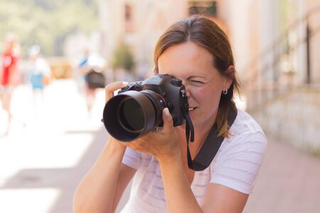Young beautiful tourist woman taking photographs with digital photo camera. Wanderlust Concept. Stock Photo
