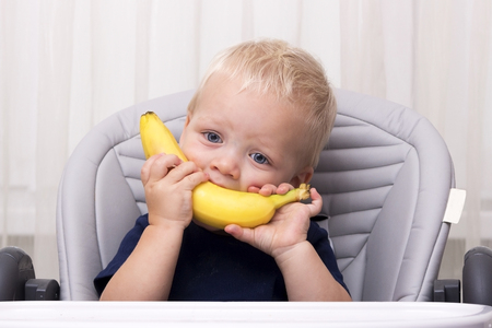 smudgy: Cute one year old toddler eating a banana and sitting in the baby chair. Funny kid with banana smile