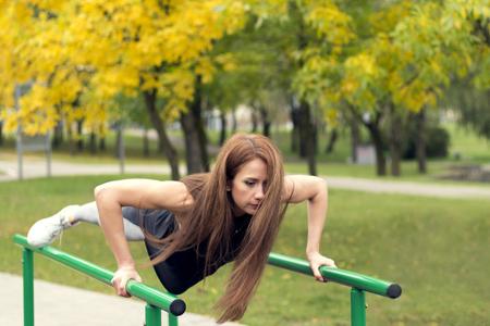 Beautiful female athlete exercising on parallel bars, doing push-ups