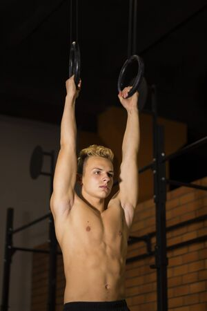 Young fit man pulling up on gymnastic rings. Bodybuilder in the gym is training, the dark background. Motivation.