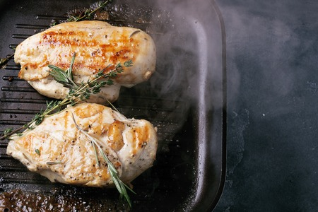 Fried chicken breast with rosemary on the grill pan with smoke. Top view. Copy space. Stockfoto